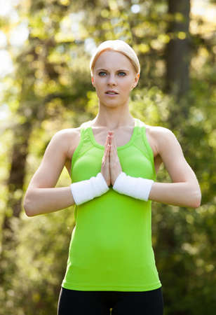 Portrait Of Young Blonde Woman Practicing Yoga In Park photo