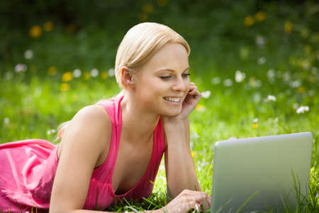 Happy Beautiful Woman Lying On Grass Using Laptop photo