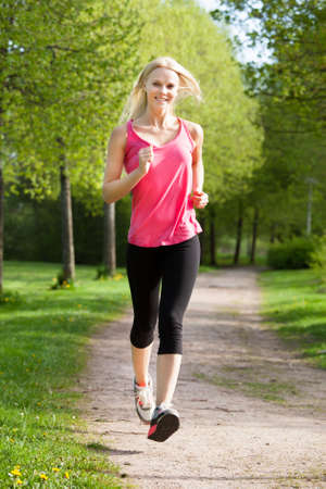 Portrait Of Happy Young Woman Jogging In Park photo