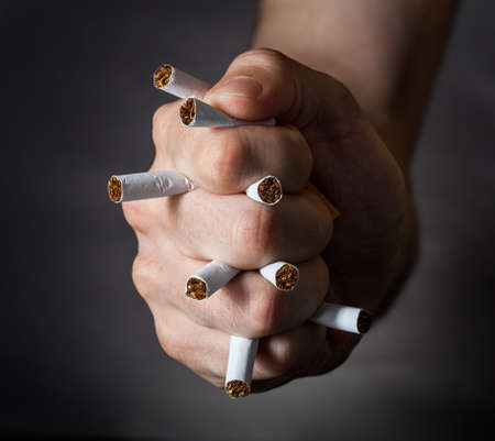 protrude: Male Fist Piercing Cigarettes Over Black Background