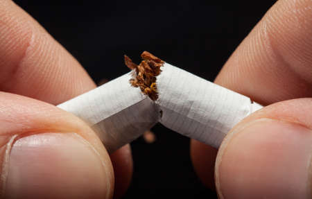 nicotine: Close-up Of  Hand Breaking Cigarette Over Black Background