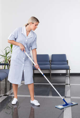 sirvienta: Limpieza que limpia el suelo con la fregona en oficina