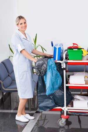 pulizia pavimenti: Giovane cameriera felice di pulire il pavimento con Mop