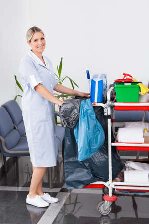 Office uniforms: Joven Dama feliz que limpia el suelo con la fregona