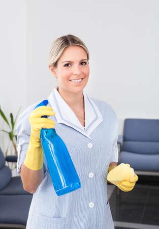 mujer limpiando: Joven Dama feliz celebraci�n de la botella y de la esponja Foto de archivo