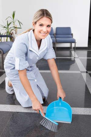 mujer arrodillada: Feliz limpieza Barrer el suelo con plumero y la bandeja de polvo