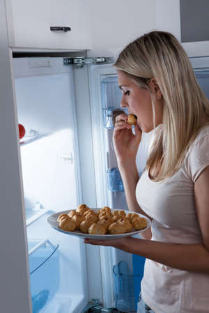 Young Woman Eating Cookies From Refrigerator At Night photo