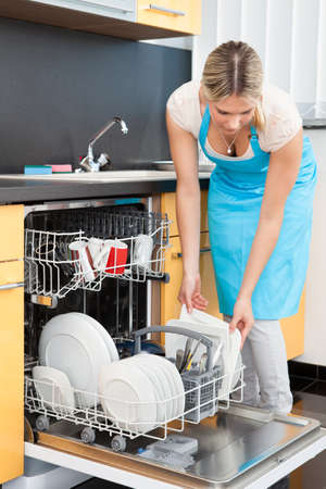 Happy Woman Putting Utensils In Dishwasher For Cleaning Stock Photo - 21043955