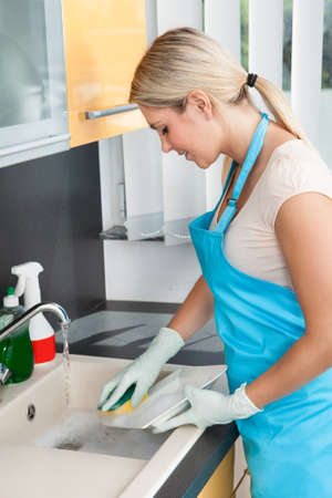 Young Woman Washing Plate In The Kitchen photo