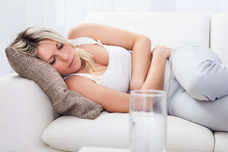 diarrea: Retrato de mujer con dolor de estómago sofá sentado