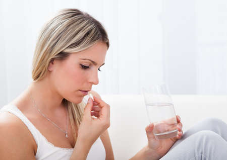 Close up of a woman taking pills holding glass of water photo