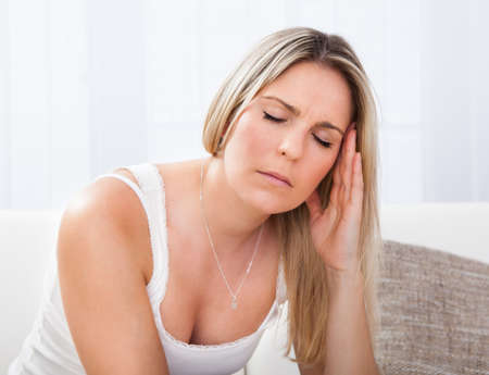 Woman with a migraine sitting holding her throbbing head photo