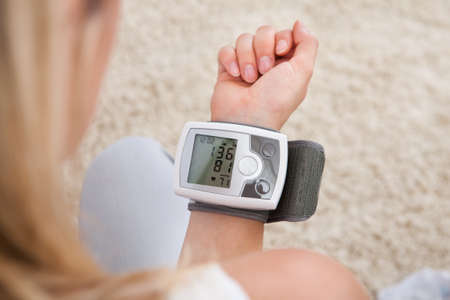 blood pressure cuff: Portrait of young woman measuring her blood pressure