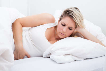 hormonal: Portrait of woman with stomach ache lying on bed