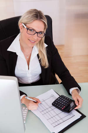 Young Businesswoman Calculating Data In Her Office Stock Photo - 21043908