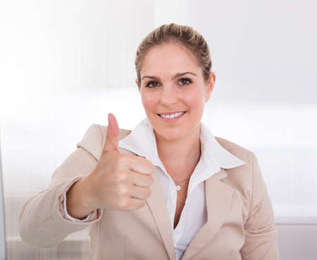 hand gestures: Portrait Of Happy Businesswoman Showing Thumb Up Sign In Office