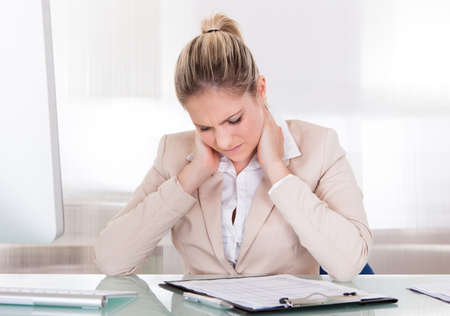 working stiff: Young Businesswoman Suffering From Neck Pain At Office