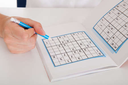 contemplated: Closeup Of The Young Woman Solving Sudoku