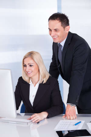 Happy Businessman And Businesswoman Looking At Computer photo