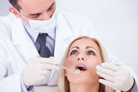 dental care: Male Dentist Examining Female Patient In Clinic