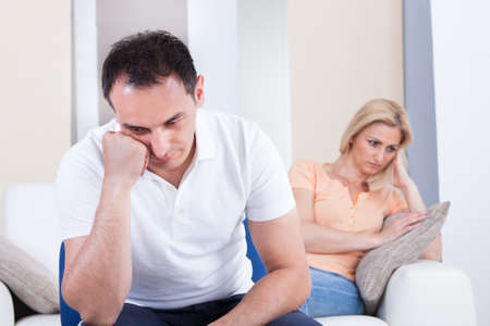 personas discutiendo: Retrato de mediados de adulto sentado en el sofá después de la pelea