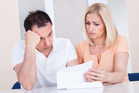 hombre preocupado: Retrato de pareja sorprendido mirando a Bill Foto de archivo