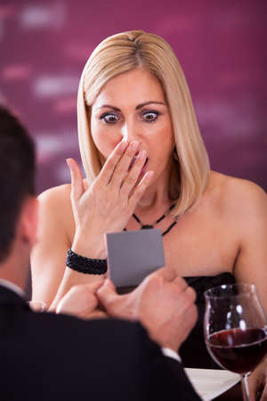 Surprised Woman Looking At Wedding Ring In Restaurant Stock Photo - 21234543