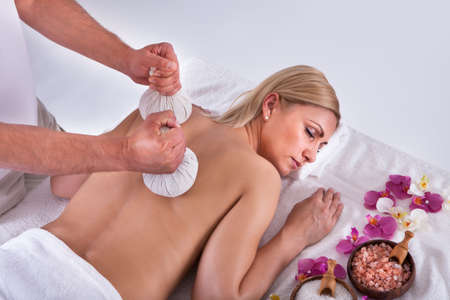 Beautiful Young Woman Getting Herbal Therapy At Spa Salon photo