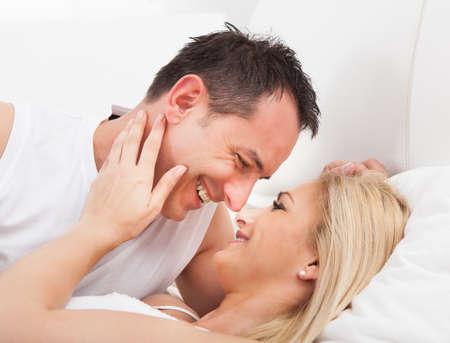 enamorados en la cama: Retrato de los amantes que se abrazan en la cama Foto de archivo