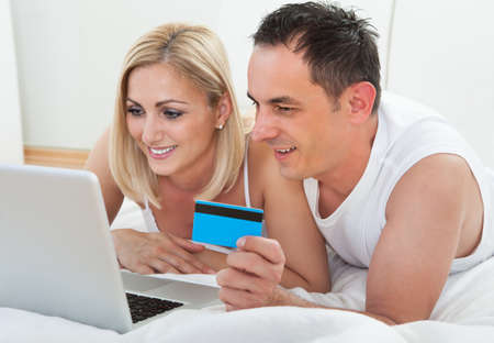 Couple In Bedroom Shopping Online Holding Credit Card photo