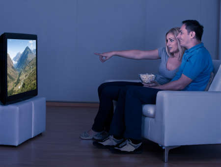 Happy Couple Eating Popcorn And Watching Television photo