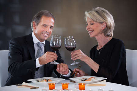 lifestyle dining: Happy Mature Couple Toasting Wine In A Elegant Restaurant Stock Photo