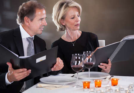 Mature Couple Sitting In Restaurant Woman Choosing Menu photo
