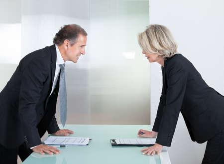 personas discutiendo: Empresario Y Empresaria madura buscando unos a otros con Angry