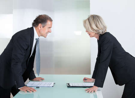 debating: Mature Businessman And Businesswoman Looking At Each Other With Angry