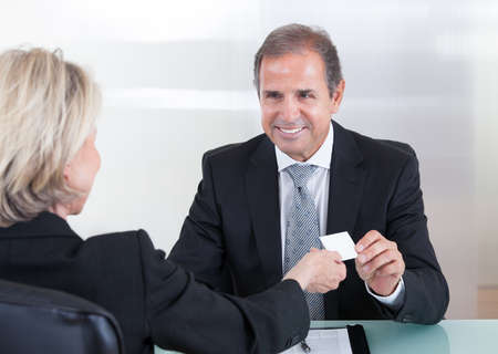 Happy Mature Businesspeople Exchanging Visiting Card In Office photo