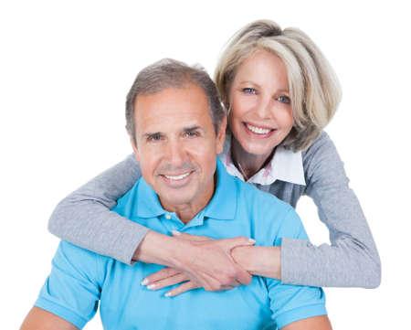 parejas felices: Mujer abrazando hombre maduro de detrás que se sienta en bola de Pilates