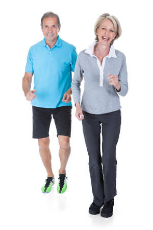 Happy Mature Couple Jogging Over White Background photo