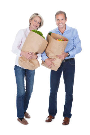 Happy Mature Couple Shopping Fresh Vegetable Over White Background Stock Photo - 21234759