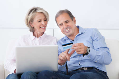 Happy Mature Couple Shopping Online On Laptop At Home photo