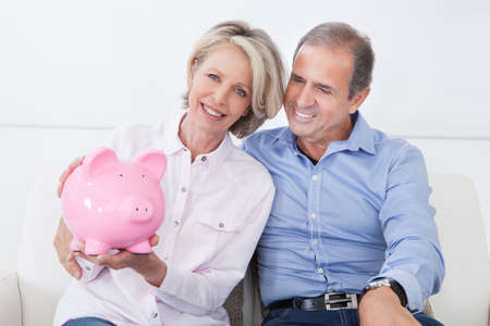 income tax: Happy Mature Couple Calculating Coin In The Piggybank