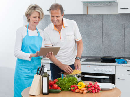 Mature Man And Woman Looking At Recipe Tablet While Cooking In Kitchen photo