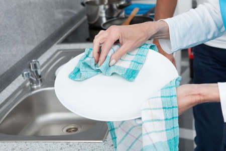 Close-up Of Woman Wiping Plate With Dishcloth photo