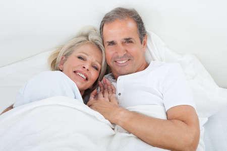 ベッドを一緒に寝ているに幸せな先輩カップルの肖像画 写真素材