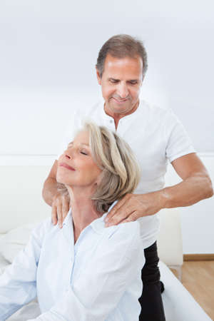 Mature Man Massaging Womans Shoulder In Bed photo