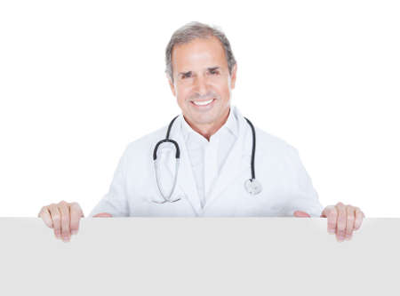 Portrait Of Mature Doctor Holding Placard Over White Background photo