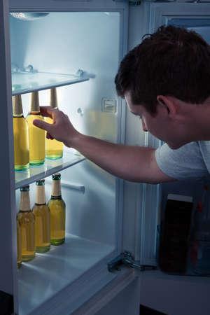 refrigerador: Hombre que elige la botella de cerveza de una nevera Foto de archivo