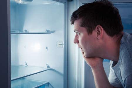 refrigerador: Retrato de un hombre hambriento en busca de comida en el refrigerador