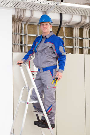 climbing ladder: Young Worker Man With Hard Hat standing on ladder Stock Photo