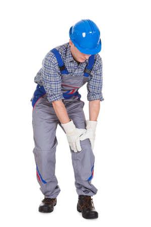 hard worker: Lavoratore di sesso maschile affetti da dolore al ginocchio isolato su sfondo bianco